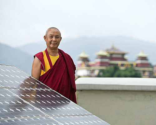 A monk poses for a photograph with some solar panels at Kopang Monastery. Kopang Monastery in Kathmandu, Nepal has several solar panels on the roof that provide light to the garden and the monastery.